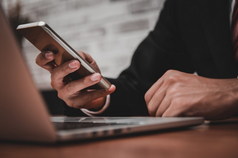 Close up of businessman working in his office with smart phone,d